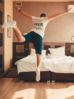 Homme qui saute sur un lit